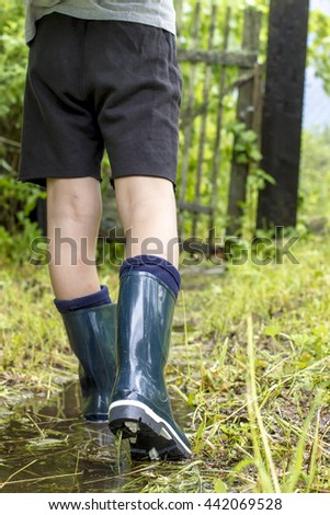 Child in shining gumboots goes on a footpath on the puddle close up, on a rainy summer day - stock photo