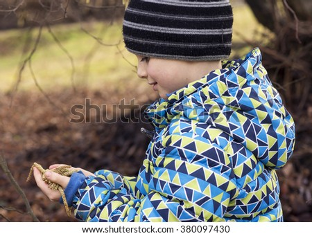 Child in spring nature exploring catkins in his hands. - stock photo