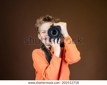 Child in studio with professional camera. Boy using a camera on brown background. - stock photo