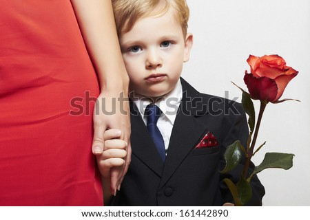 child in suit with mother. flower. red dress. family. fashionable little boy. red rose. take the hand - stock photo