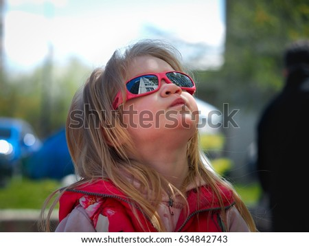 Child in sunglasses on the street. Portrait. Reflection of buildings