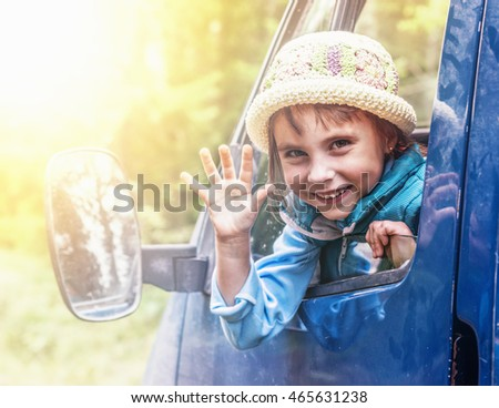 Child in the car at sunset.