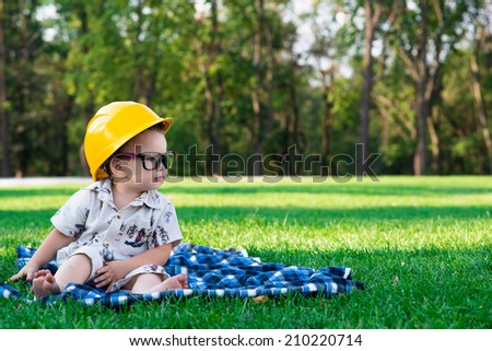 child in the construction helmet and glasses playing on the grass - stock photo