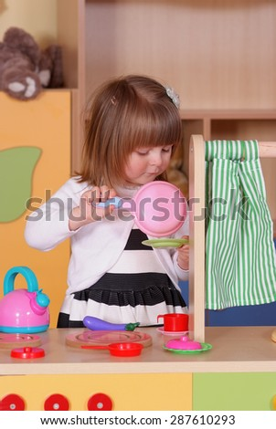 Child in the nursery is playing in cooking