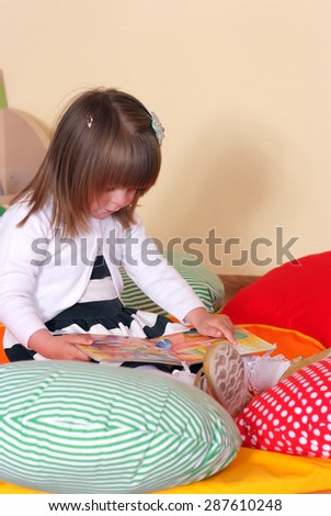 Child in the nursery reading a book - stock photo