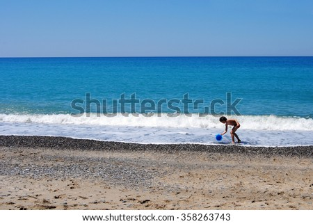 child in the sea playing with bucket