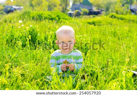 child in the spring park on a background of green grass and foliage
