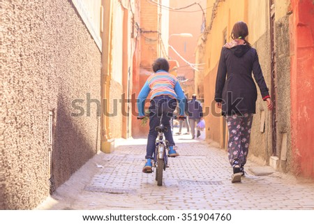 child in typical Street Scene In The medina  Of Marrakesh, Morocco - stock photo