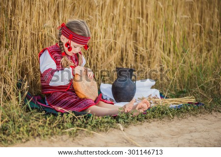 Child in Ukrainian national costume sitting near the wheat