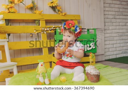 Child in Ukrainian national costume with Easter cake. Text happiness. - stock photo