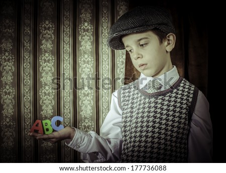 Child in vintage clothes hold multicolor letters a b c