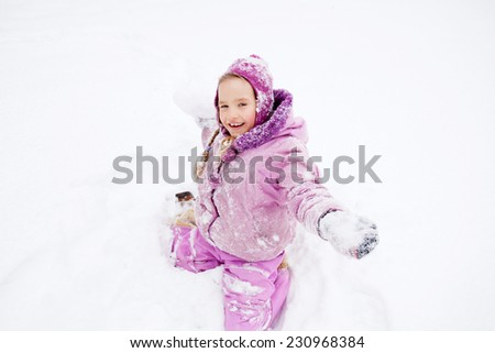 Child in winter. Happy girl playing snowballs - stock photo