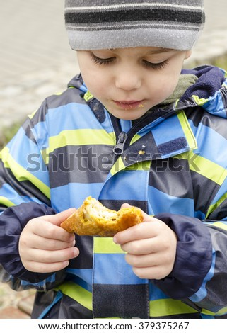 Child in winter hat eating bread roll or pastry  at street or park, aid or poverty concept.