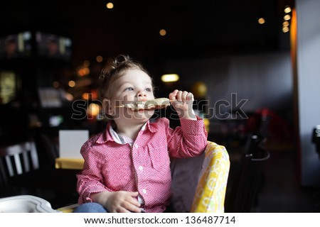 Child is biting kebab in a high chair at a restaurant - stock photo