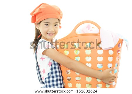 Child is holding a laundry basket - stock photo