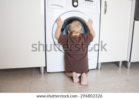 Child is looking into the washing machine