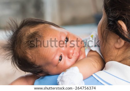 Child is lying on his mother's shoulder.
