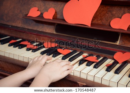 Child is playing on a piano on Valentine's Day, close-up, face is not visible. Point of view shot