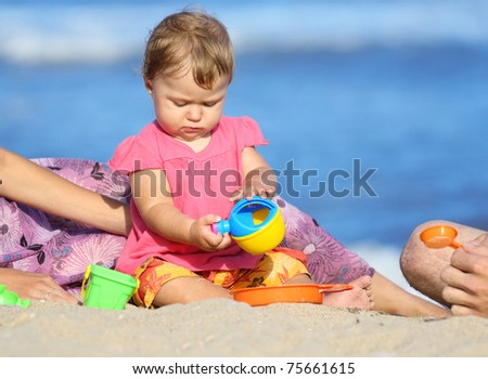 child is playing on the shore of the sea