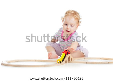 child is playing with wooden train isolated on white - stock photo