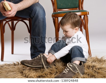 Child is putting on a big father's shoe. - stock photo