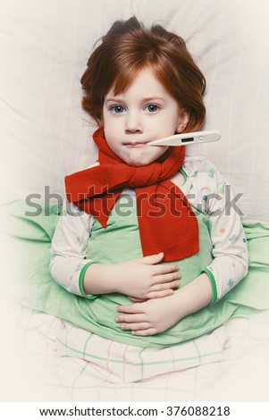 child is sick with a thermometer in mouth lying on the bed