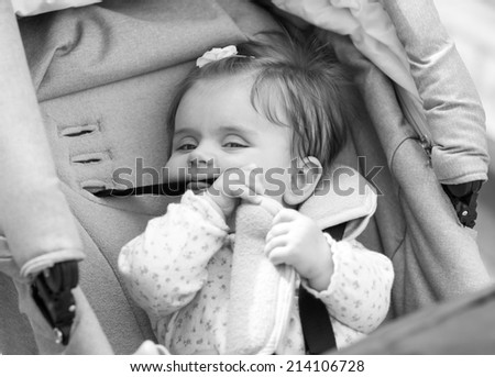 child is sitting in a carriage. black & white - stock photo