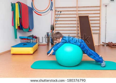 Child is therapeutic exercises in the gym  - stock photo