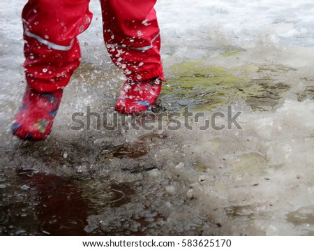 child jumping for puddles on the roads thaw in the end of winter