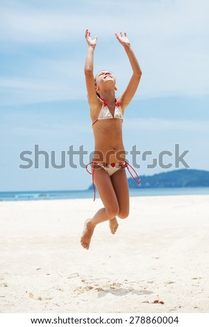 Child jumping on a tropical beach during summer vacations