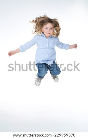 child jumps high on white and isolated background - stock photo