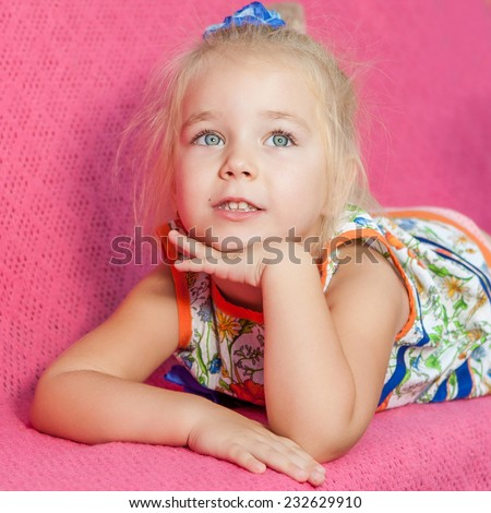 Child.  Kid. Adorable little girl laying on pink  background and looking up - stock photo