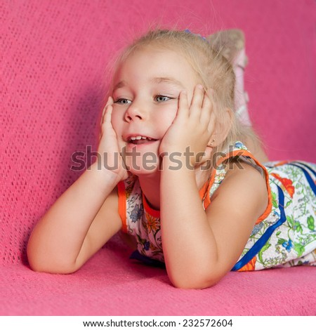 Child.  Kid. Adorable little girl lying on pink  background. Capricious, cheerful. - stock photo