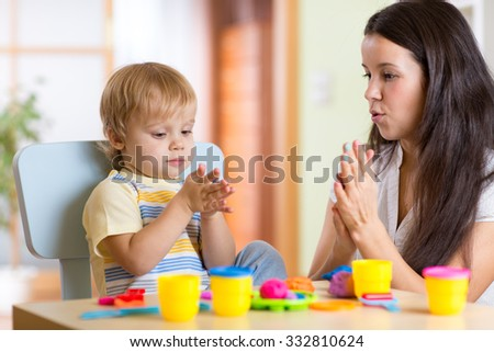 child kid boy and his mom playing colorful clay toy at nursery or kindergarten - stock photo