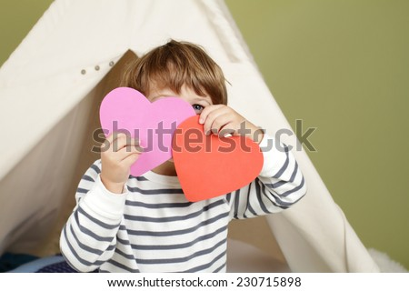 Child, kid, engaged in a Valentine's Day arts and crafts activity - stock photo