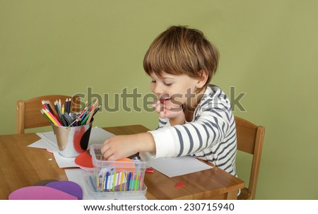 Child, kid engaged in arts and crafts activity, creative learning and education concept - stock photo