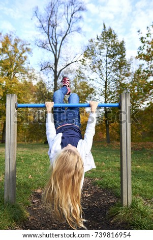 Child kid girl upside down on a park playground gym game