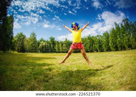 child kid girl with party clown blue wig funny happy open arms expression and garlands is jumping in the park - stock photo