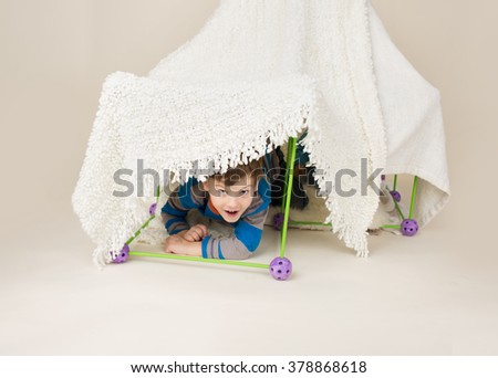 Child, kid, playing with a tent or fort made out of blankets - stock photo