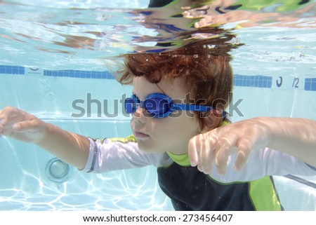 Child, kid, swimming in pool underwater, summer or sports theme