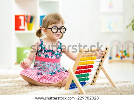 child kid weared glasses playing with abacus toy indoor - stock photo