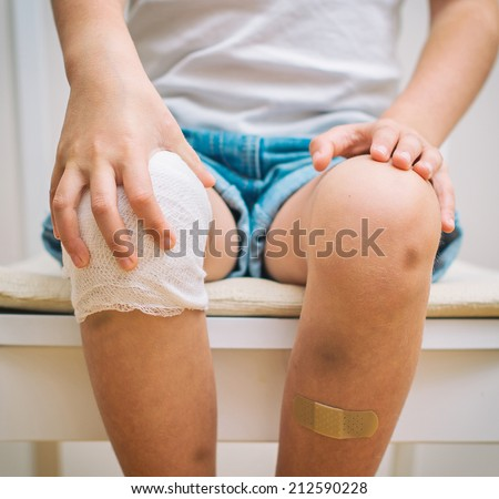 Child knee with adhesive bandage, bruise and gauze bandage. - stock photo