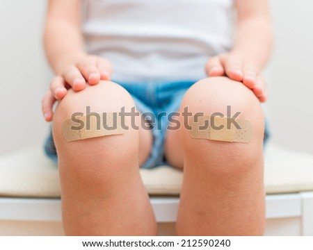 Child knee with an adhesive bandage. - stock photo