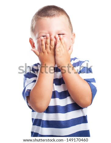 Child laughing and covering his face with hands on white