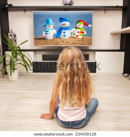 Child laying on the floor and watching TV at home - stock photo