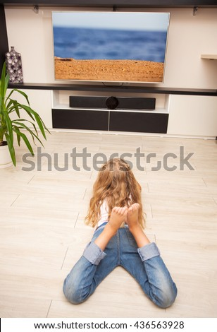 Child laying on the floor and watching TV at home