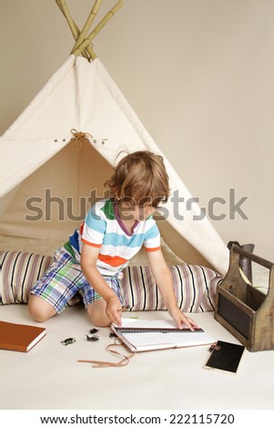 Child learning and education during indoor play: drawing and writing - stock photo
