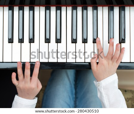 Child learning to play the piano. Top view. - stock photo