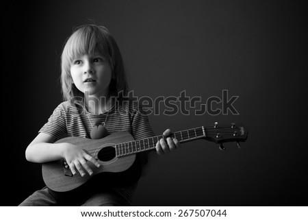 Child learning to play the ukulele - stock photo