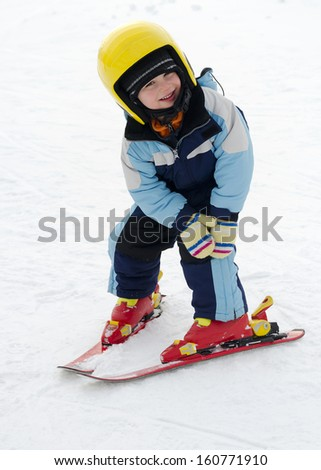 Child learning to ski in winter skiing resort practicing the correct moves.  - stock photo